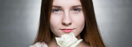 sensible: Young beautiful woman with a white rose, light background, panorama