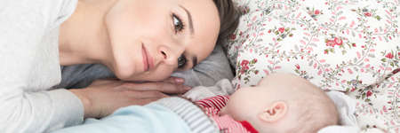 motherly love: Panoramic picture of a young mother looking with love at a newborn baby sleeping next to her