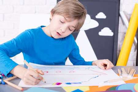 beside table: Creative boy sitting beside table, drawing a picture
