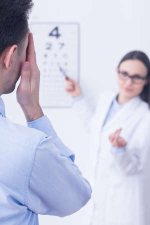 medical choice: Man during visual examination, woman optician in white uniform standing in the background