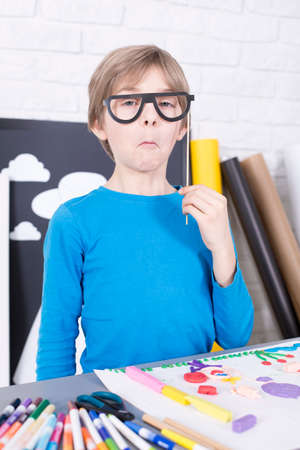 beside table: Boy with a serious face holding paper glasses, standing beside table
