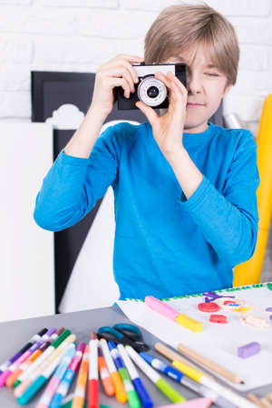 beside table: Boy holding a camera, standing beside table in light interior