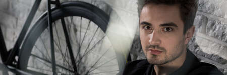 beau mec: Photo panoramique d'un jeune homme regardant la caméra et assis à côté de son vélo