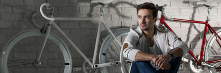 bike cover: Panoramic picture of a young handsome man sitting in front of two bikes Stock Photo