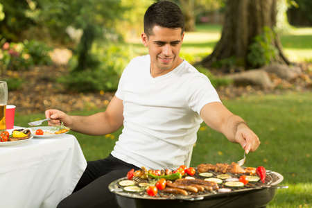 seconds: Hungry young man taking a seconds of barbecue food