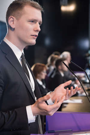 lectern: Young businessman at podium giving press conference Stock Photo