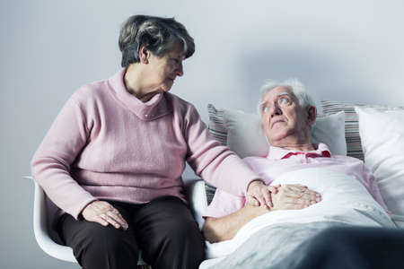 hospice: Senior woman supporting her ill husband lying in a hospital bed Stock Photo