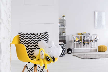 designer baby: Cuddly mascots seated on a designer chair in a baby room Stock Photo