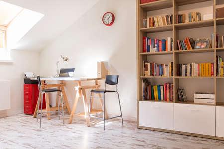 Shot van een moderne studie met een bureau en een boekenplank