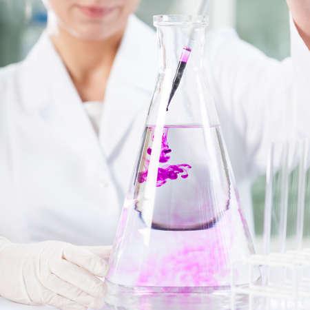 chemist: Chemist putting purple liquid into the flask