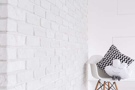 designer chair: White designer chair with pillows, standing aside white brick wall