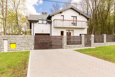 Shot of a white detached house with a driveway and a fence