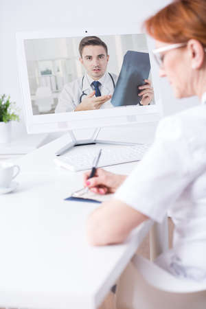 taking video: Shot of a doctor taking notes during a video conversation with a colleague Stock Photo