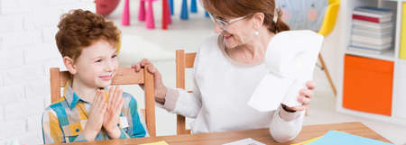 therapist: Female speech therapist is showing to a boy a figure of letter Stock Photo