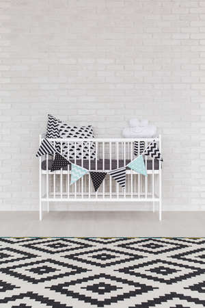 room wall: Cot by white brick wall with scandinavian carpet in the foreground