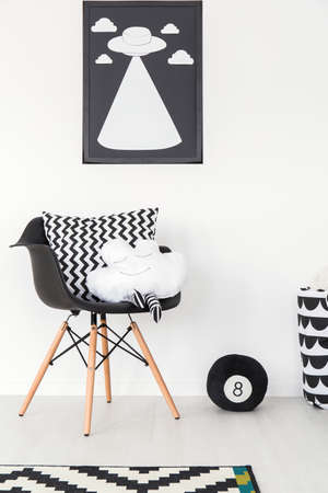 designer baby: Black chair standing by white wall decorated with UFO print Stock Photo