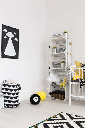 designer baby: Corner of a bright infant room furnished in scandinavian style