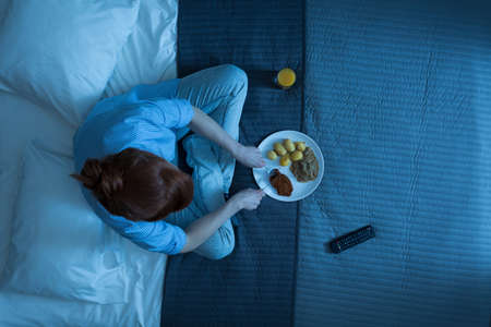 Shot of a woman sitting on a bed and eating dinner Stockfoto