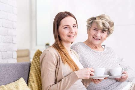 mujeres ancianas: Primer plano de una mujer joven tomando el té con su abuela en un interior luminoso