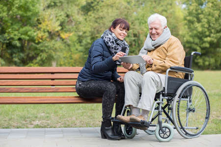 Disabled retiree in park with young carer