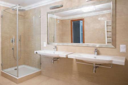washbasins: Shower and two washbasins in beige bathroom Stock Photo