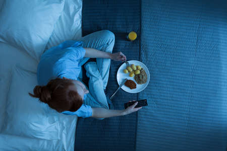 Top view of a woman sitting on a bed, eating dinner and holding a remote control Stock Photo