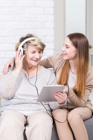 assisted: Shot of a grandmother listening to music from tablet, assisted by her granddaughter