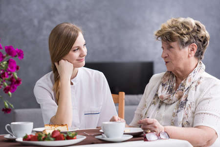 Shot of a young caregiver talking with her senior patient at the table Stock Photo