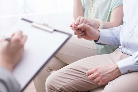 difficulties: Couple with relationship difficulties holding hands during session with marriage counselor