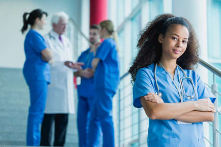 internship: Afroamerican medical student standing on stairs, in the background group of students talking with a doctor
