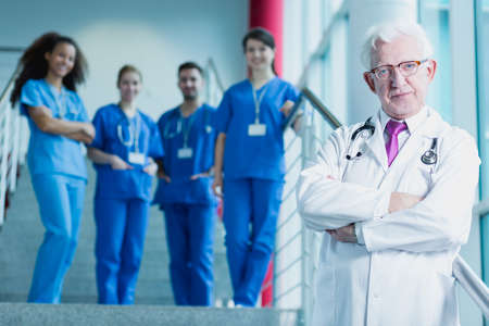 trainees: Mature doctor in white medical uniform with stethoscope, in the background group of medical trainees