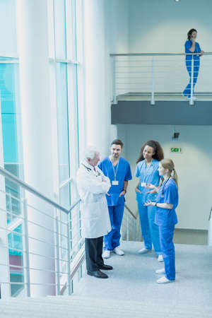 Group of medical students in blue uniforms talking with mature doctor Stock Photo