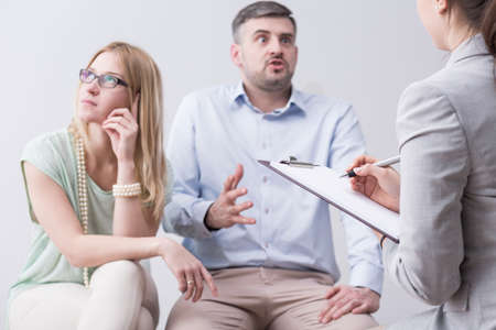 couples therapy: Bored woman and furious man trying to save marriage during couples therapy