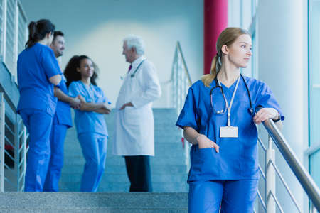 traineeship: Young medical student with a stethoscope standing on stairs, in the background group of students talking with a doctor in uniform