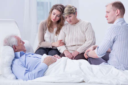 Shot of a senior man on a hospital bed surrounded by his family