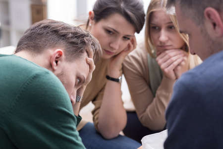 consoling: People talking together and comforting young man during group therapy session