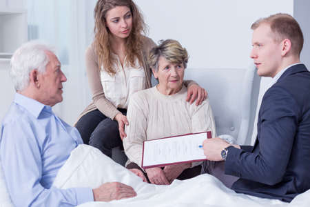 Shot of a family listening to a young man holding a last will form Stockfoto