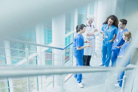 estudiantes medicina: Grupo de estudiantes de medicina en discusiones con un dcotor en el uniforme blanco