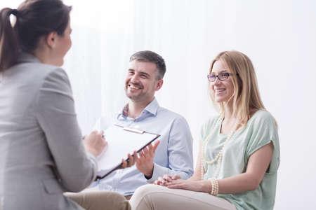 llenado psicoterapeuta en el cuestionario sesión de psicoterapia con el matrimonio joven feliz Foto de archivo