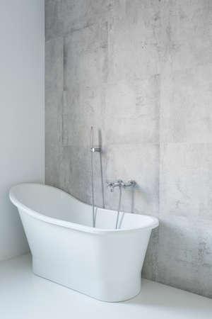 modern bathroom: White, big bathtub in modern bathroom with decorative concrete wall. Stock Photo