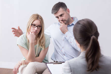 despondency: Young unhappy married couple with problems wants to reconcile on psychotherapy session