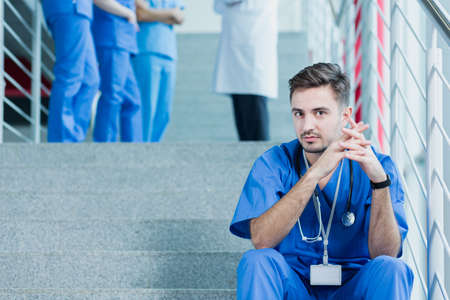 Young student of medicine sitting on a stairs, in the background group of people in medical uniforms