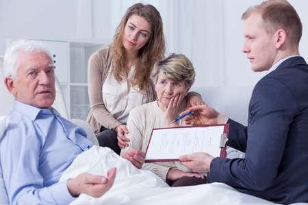 Schuss eines älteren Mannes, der Unterzeichnung seinen letzten Willen und seine Familie sitzt um sein Bett