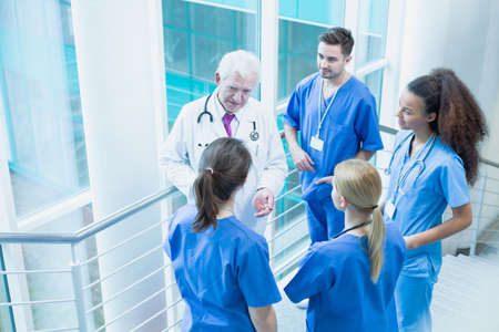 traineeship: Students of medicine talking with a doctor in medical uniform Stock Photo