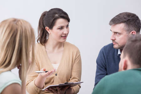 people problems: Young, female psychotherapist and people discussing their private problems Stock Photo