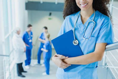 traineeship: Afroamerican medical student smiling, in the background group of trainees discussing with doctor Stock Photo