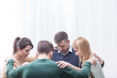 Grupa ludzi trzymających się wzajemnie w ramionach tworzących krąg Zdjęcie Seryjne