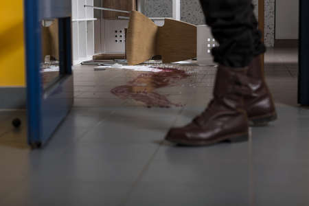 tapes: Close up of a mans legs, bloody splash on the floor Stock Photo