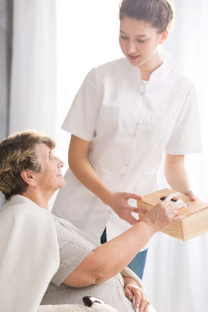 homecare: Young carer in white uniform and senior lady