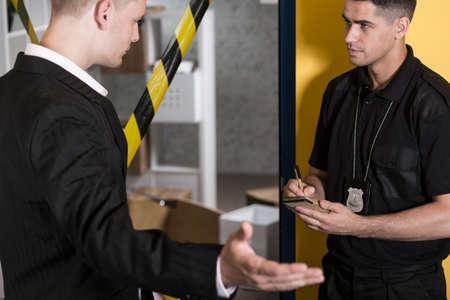 Testimone dando statment a un poliziotto, poliziotto facendo note